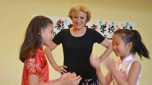 Oberbürgermeisterin Charlotte Britz schaut zwei Mädchen bei einem chinesischen Klatschspiel zu